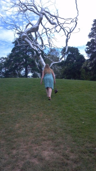 Holly walking towards a silver tree sculpture